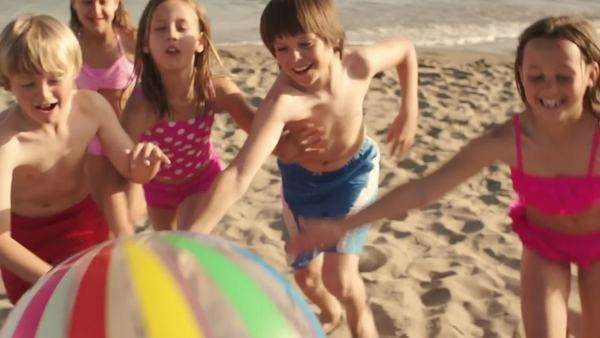 Five children running towards camera pushing beach ball on beach. Royalty-free stock video