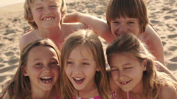 Close up of five children on beach facing camera and laughing. Royalty-free stock video