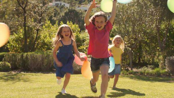Slow motion of five children running towards camera with balloons. Royalty-free stock video