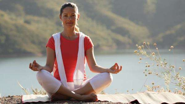 Woman sitting by lake practising yoga Royalty-free stock video