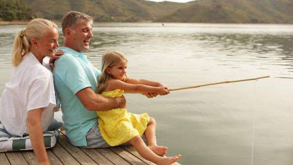 Mature couple with grandchild fishing by lakeside Royalty-free stock video