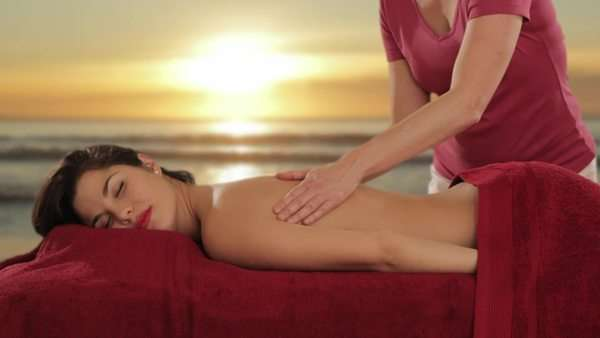 young woman having massage, sunset and beach background Royalty-free stock video