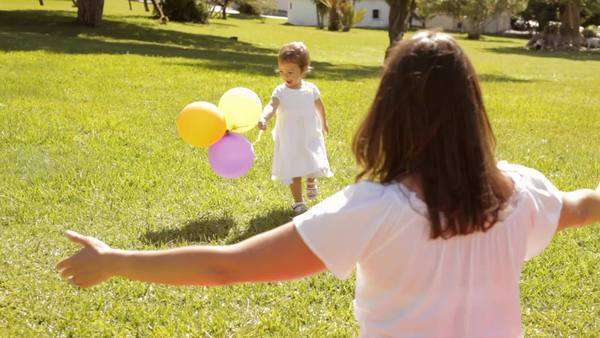 mother and baby playing with balloons in park Royalty-free stock video