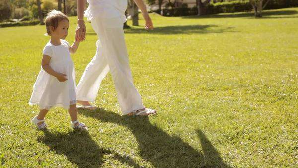 pan shot of mother and baby walking in park Royalty-free stock video