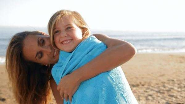 mother cuddling daughter on beach in blue towel Royalty-free stock video