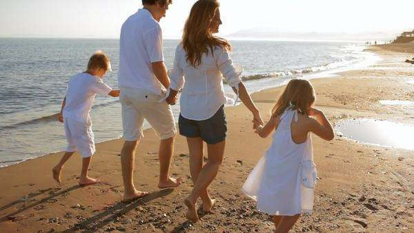 pan shot of family walking away from camera on beach Royalty-free stock video
