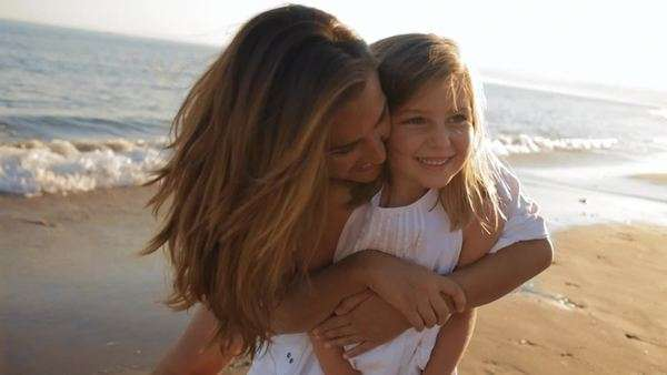 mother cuddling daughter on beach Royalty-free stock video