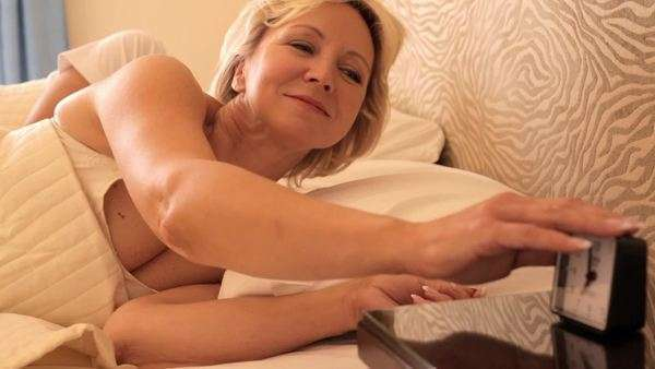dolly shot of senior couple asleep in bed woman waking and turning off alarm Royalty-free stock video