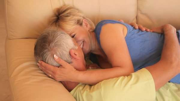 pan shot of senior couple falling on sofa and hugging Royalty-free stock video