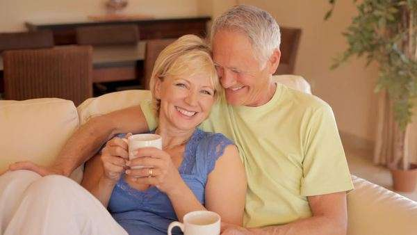 senior couple on sofa drinking tea or coffee Royalty-free stock video