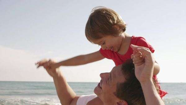 Happy little girl on her father's shoulders at beach. Royalty-free stock video