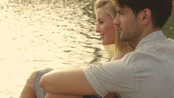 Dolly shot of couple sitting on dock beside lake. Royalty-free stock video
