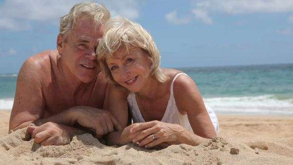 Portrait of senior couple laying in sand at beach Royalty-free stock video