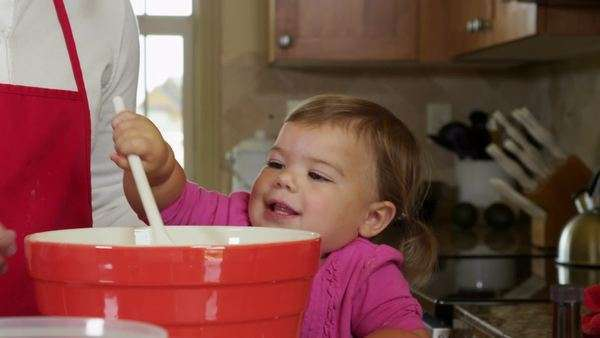Young girl helping Mom in the kitchen Royalty-free stock video