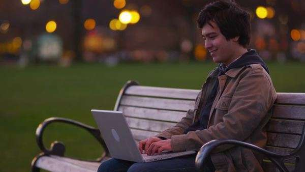 Young man sits on park bench using laptop computer Royalty-free stock video