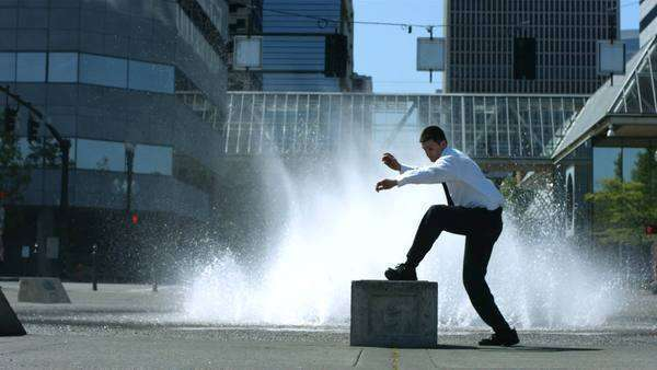 Business man does flip in front of city fountain Royalty-free stock video