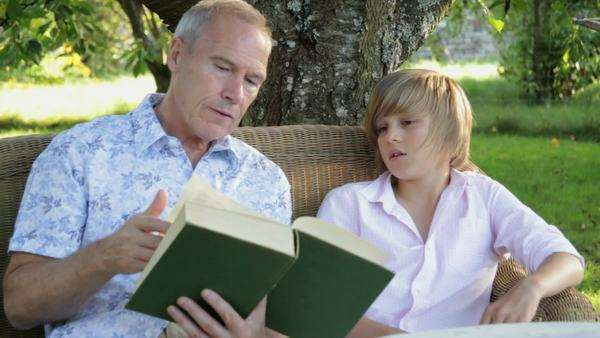 Father and son sitting on bench in garden reading and talking Royalty-free stock video