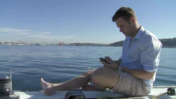 Man uses smartphone while on a sail boat on the Puget Sound in Seattle, Washington  Wide shot Royalty-free stock video