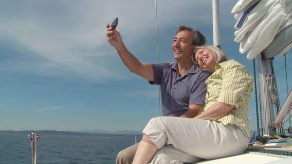 Mature couple photograph themselves with a smartphone while sailing on the Puget Sound in Seattle, Washington Royalty-free stock video