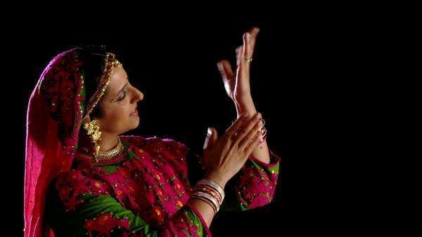Attractive Indian woman in traditional dance costume makes gestures with her hands, then looks to the camera and smiles  Recorded against black background Royalty-free stock video