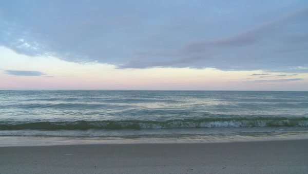 Dawn view of waves breaking on a sandy beach on a summer's day  Looping clip recorded in Frankfort, Michigan, on Lake Michigan Royalty-free stock video