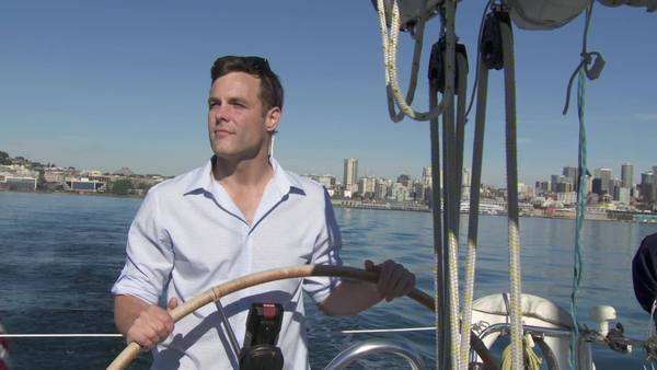 Man takes the helm of a sailboat with the city skyline behind him  Filmed on the Puget Sound in Seattle, Washington Royalty-free stock video