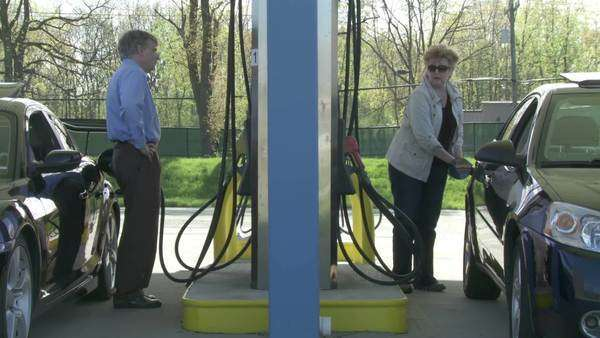 Two motorists fill up their cars at a self-service gas station  Full length shot with camera moving on jib Royalty-free stock video