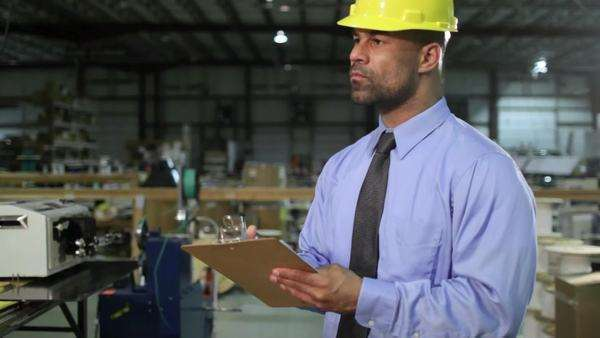 Business man checks inventory in an industrial warehouse setting, then turns and smiles to camera  Camera moves on jib Royalty-free stock video