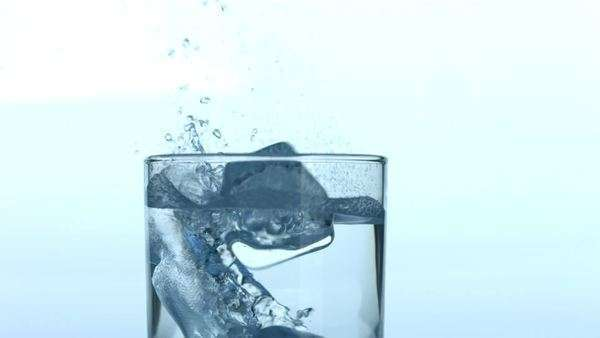 Ice cubes splashing into glass of water Royalty-free stock video