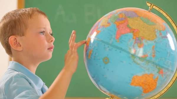 Young boy in classroom looking at globe Royalty-free stock video