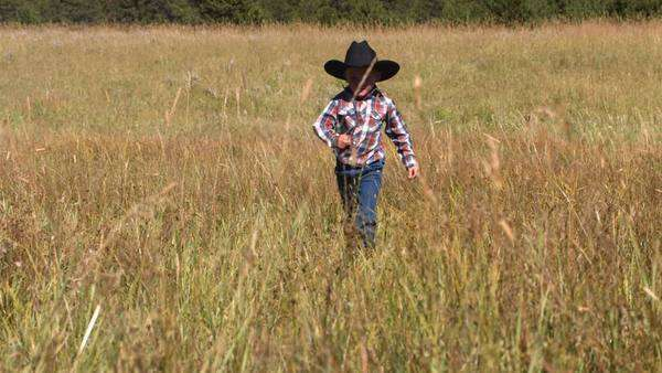 Young cowboy runs in grassy field, slow motion Royalty-free stock video
