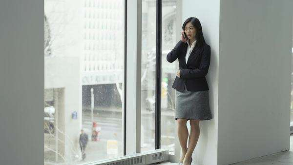 An asian business woman talks on the phone and paces in a large office building Royalty-free stock video