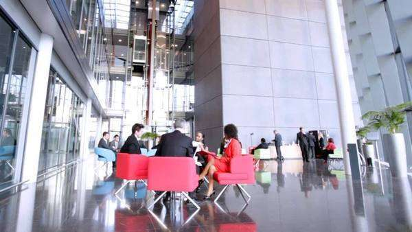Business group in relaxed meeting area of a large contemporary office building Royalty-free stock video