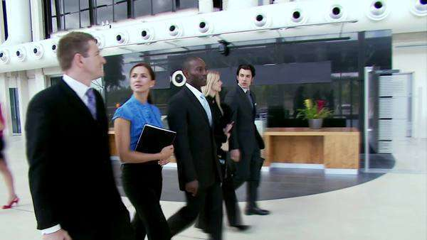 Businesspeople walk through office lobby Royalty-free stock video