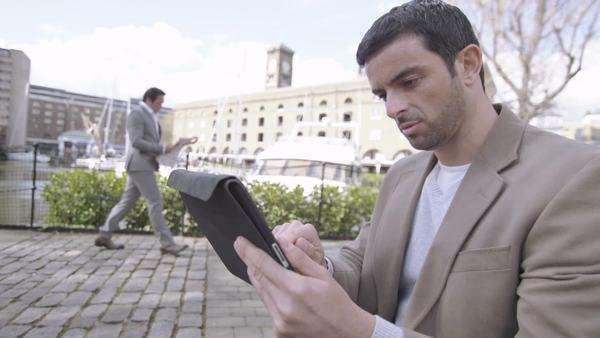 Man with digital tablet handheld device outdoors in the city Royalty-free stock video