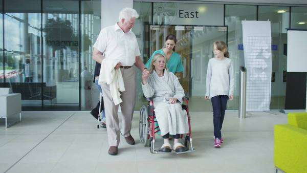 Woman with family beeing wheeled in a wheelchair Royalty-free stock video