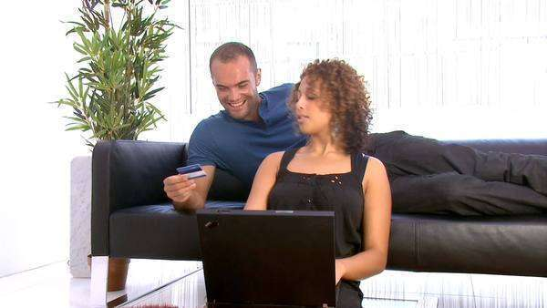 Attractive young couple with modern lifestyle relaxing together and internet browsing on a laptop Royalty-free stock video