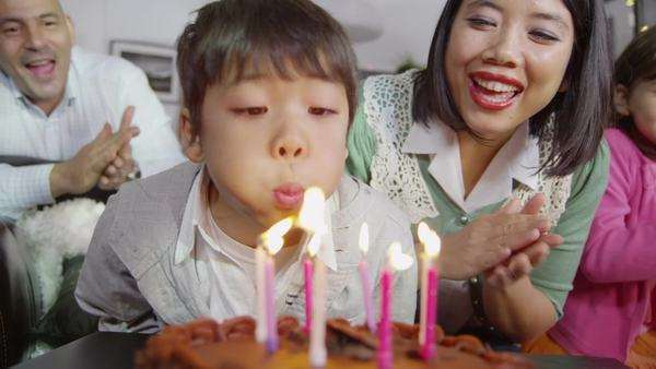 Cute young boy tries to blow out all the candles on his birthday cake but can't do it with just one breath so his family cheer him on and applaud him. In slow motion. Royalty-free stock video