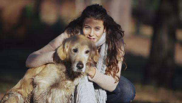 Portrait of a beautiful young woman who is spending time outdoors in a forest with her dog. In slow motion. Royalty-free stock video