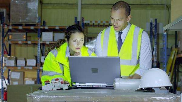 2 warehouse workers in high visibility clothing are discussing their business and looking at a laptop computer. They both look into the camera and smile. In slow motion. Royalty-free stock video