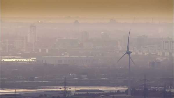 Aerial view of wind turbines in close up set against the hazy smog of a large city. Camera pulls back to reveal the vastness of the surrounding landscape and dramatic clouds at sunrise. Royalty-free stock video