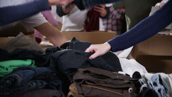 A friendly and cheerful group of charity volunteers chat amongst themselves as they sort through piles of donated clothing. In slow motion. Royalty-free stock video
