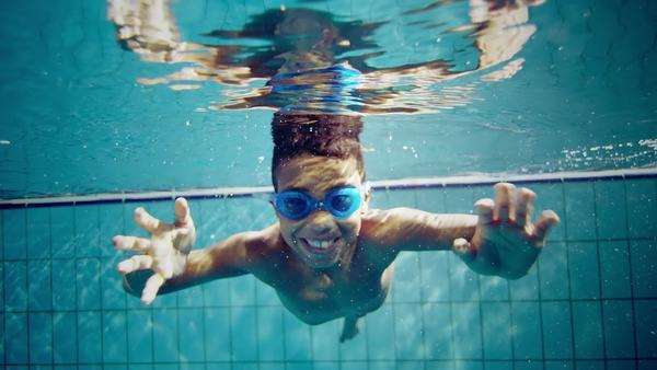 Happy cute little boy underwater is waving and smiling at the camera. Royalty-free stock video