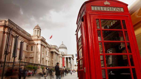 Famous London phone box, with people rushing by, Trafalgar square, London Royalty-free stock video