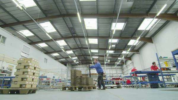 Workers in a warehouse or storage facility are moving around pallets of boxed goods and packaging materials, ready for shipping. Royalty-free stock video