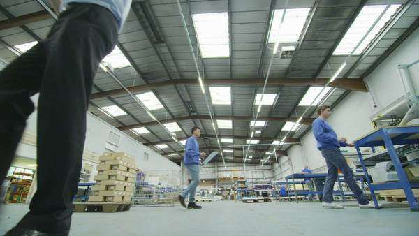Male workers in a warehouse, factory or storage facility are walking around and preparing goods ready for shipping. Royalty-free stock video