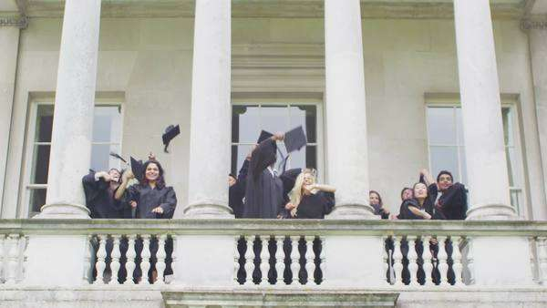 Happy and excited group of student friends on graduation day throw their caps into the air from the balcony of historic university building. In slow motion. Royalty-free stock video