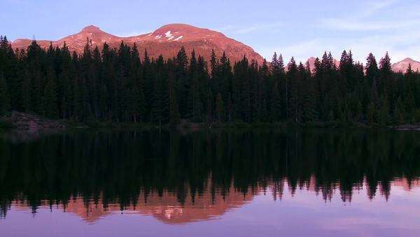 The Rocky Mountains are perfectly reflected in an alpine lake at sunset or dawn. Royalty-free stock video