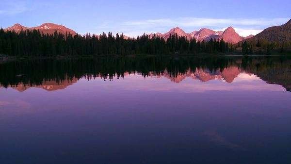 The Rocky Mountains are perfectly reflected in an alpine lake at sunset or dawn in this traveing shot. Royalty-free stock video