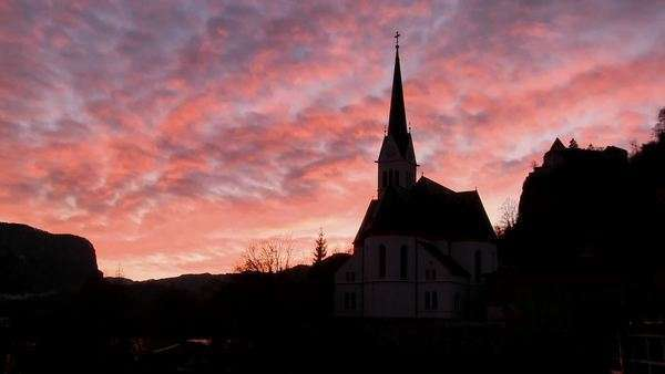 A church is silhouetted against a brilliant sky. Royalty-free stock video